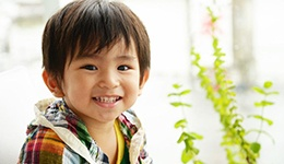 Little boy smiling by green plant