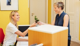 A receptionist and patient smiling