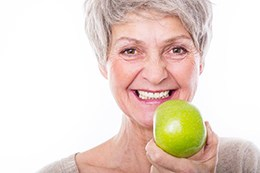 Older woman eating apple
