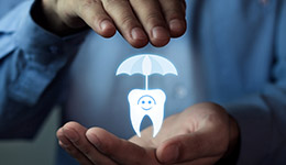 Person holding animated tooth under umbrella