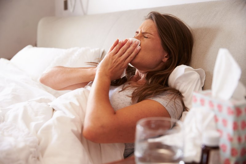a woman blowing her nose while in bed