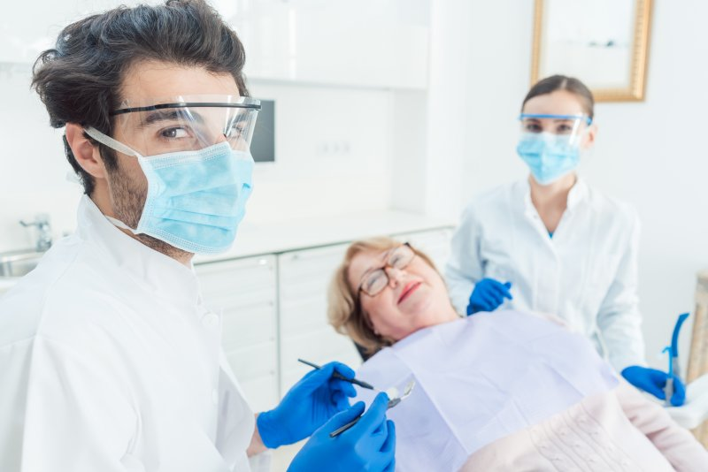 Dental team wearing PPE with patient