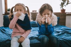 Two little girls sneezing during cold and flu season