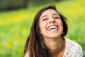 Woman smiling outside while protecting her lips from the sun