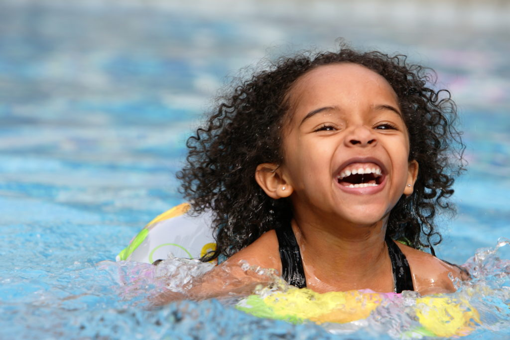 child swimming during summer